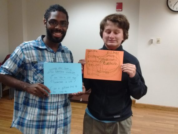 Two young men holding signs about what mentoring means to them