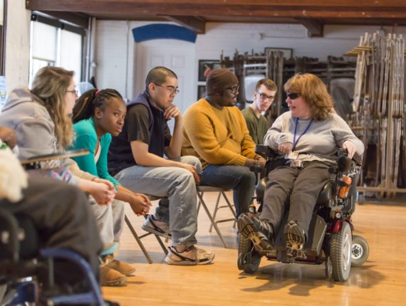 Adult in a wheelchair leading a group of teen participants in an activity