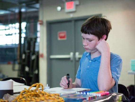 Youth with autism coloring at a table