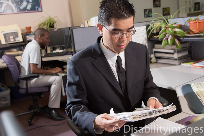 Young adult in a suit files papers in an office