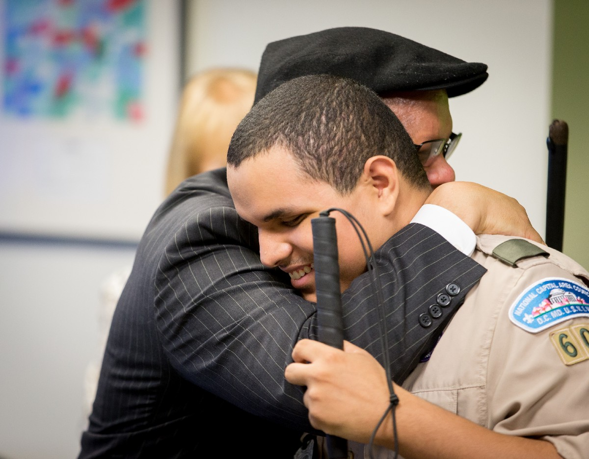 Picture of Leo Cantos hugging his Dad after providing remarks on the impact of Ollie's mentorship on him and his brothers, Nick and Steven. Photo Credit: Joshua Hoover, Department of Education.