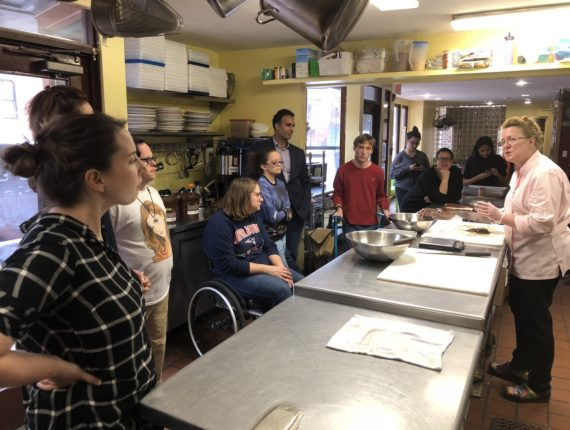 Mentors and mentees listening to Chef Napoli in a kitchen at the start of workshop.