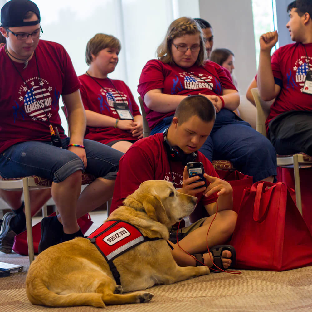 A group of student and a service dog meeting at a leadership conference