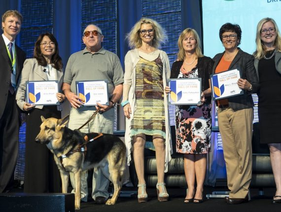 Disability mentoring hall of fame members posing on a stage with certificates after being inducted