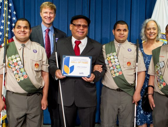 Ollie Cantos, a disability mentoring hall of fame inductee, posing with three blind Boy Scouts and the chairs of the NDMC