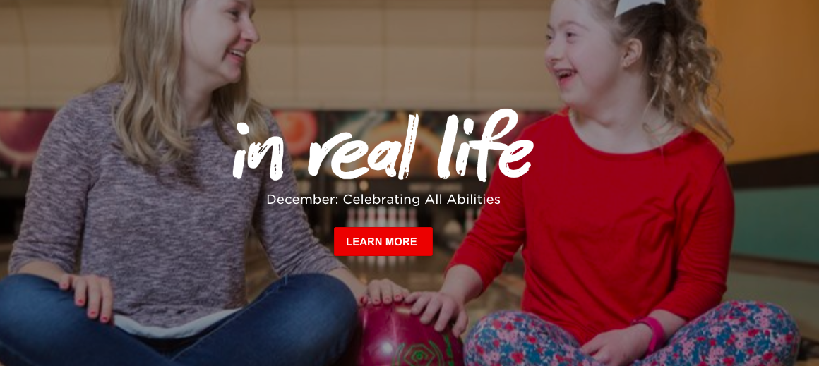 Image of white female with white girl who has an apparent developmental disability. Both smiling with ball between them.