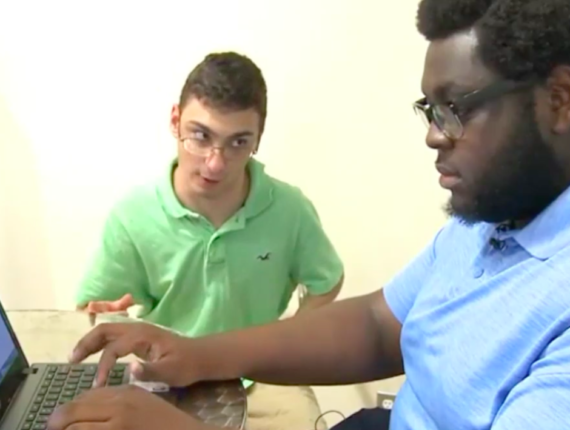 African American male peer mentor wearing a light blue shirt typing at a laptop with with white male mentee seated to his right.