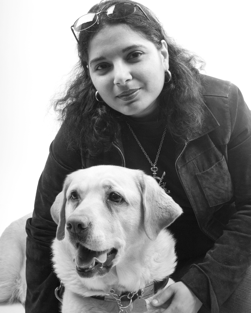 Day, an Arab-American woman with dark hair and suede jacket sitting with Veni, yellow lab guide dog