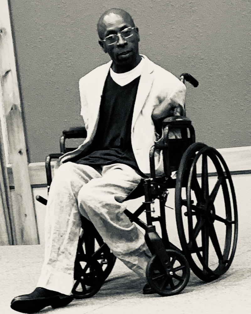 a photo of a black male state in a wheelchair on stage looking into the crowd while giving a speech