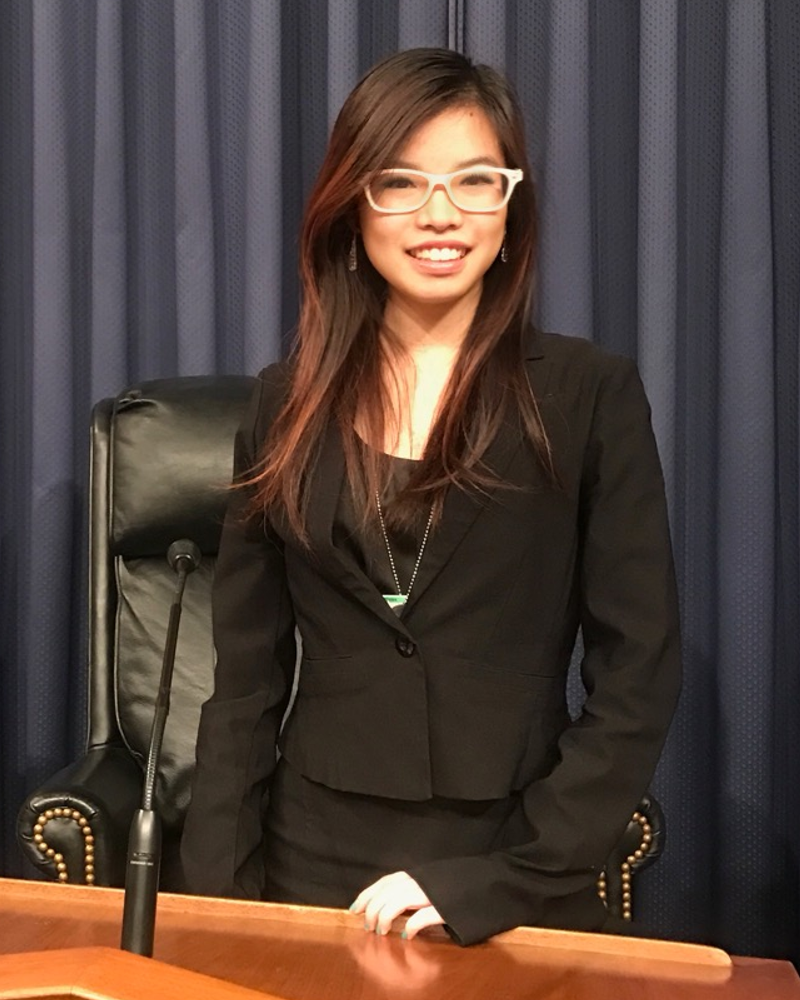Kenna Chic is an East Asian woman with brown hair and white glasses. She is smiling at the camera and wearing a black blazer and business formal black dress. She is standing at a podium with a microphone in front of her. Behind her are a black armchair and blue curtains, and on the left side of the photo is the flag of the United States of America.