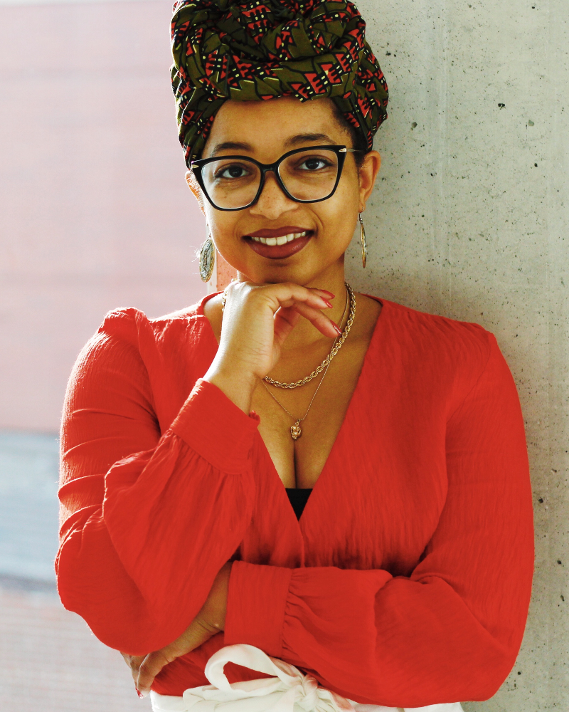 Headshot of Keri Gray. She is a Black woman wearing an orange shirt with a green and orange headwrap. She is also wearing glasses.