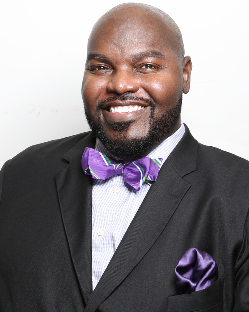 Dr. LaMondre Pough. Smiling bald black man wearing a dark suit and purple bow tie.