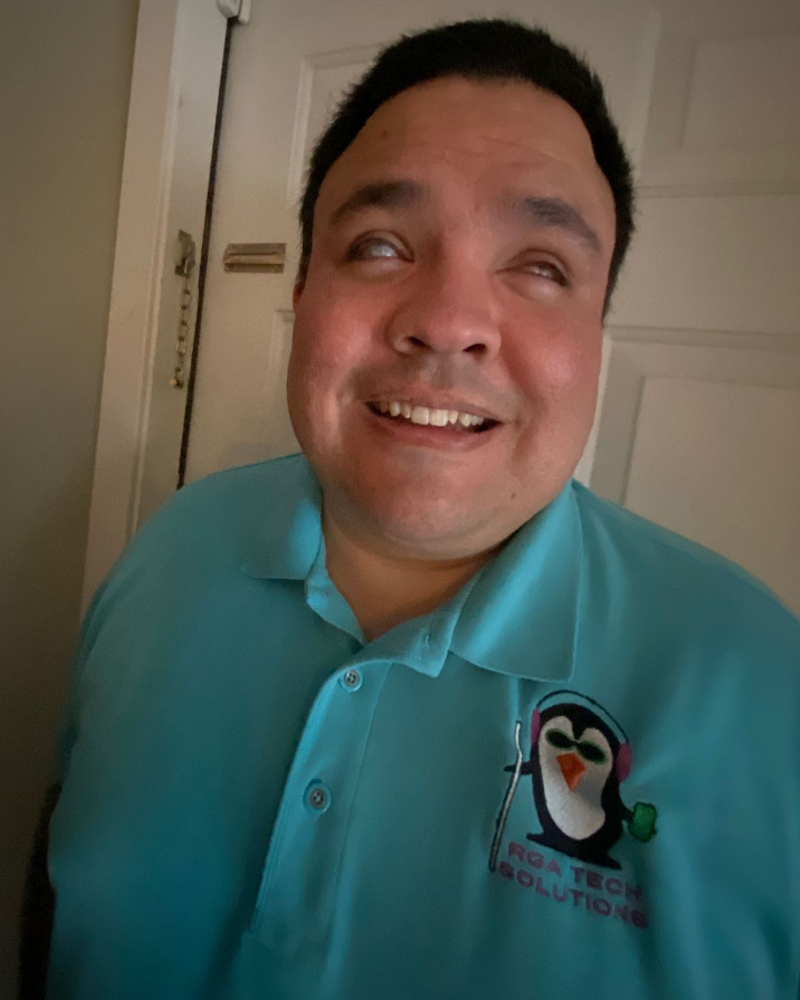 Raul has dark hair. He is wearing a blue company shirt with a logo of a penguin that says RGA Tech Solutions. The penguin is wearing headphones and is holding a phone and a cane.